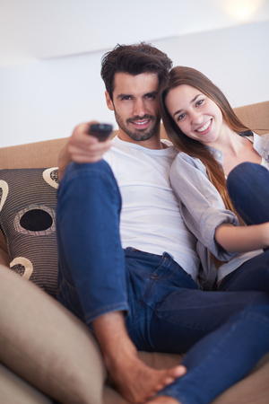 pareja viendo tv: Relaxed young couple watching tv at home in bright living room