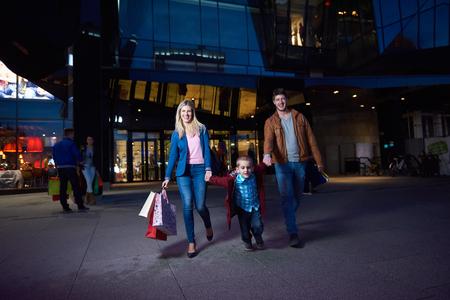 Groep Vrienden die het Winkelen van Reis samen groep van gelukkige jonge frineds genieten koopavond en wandelen op steet op de avond in met een winkelcentrum in de achtergrond