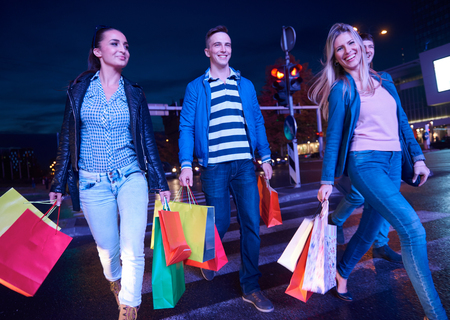 christmas shopping bag: Group Of Friends Enjoying Shopping Trip Together group of happy young frineds enjoying shopping night and walking on steet on night in with mall in background Stock Photo