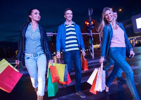 chicas de compras: Grupo de amigos que disfrutan de compras juntos grupo de j�venes felices disfrutando frineds compras de la noche y caminar en Steet en la noche con centro en el fondo