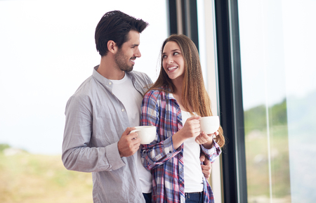 coffee houses: relaxet young couple drink first morning coffee  over big bright window in moder home villa interior