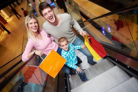 niños de compras: retrato de familia feliz joven en centro comercial