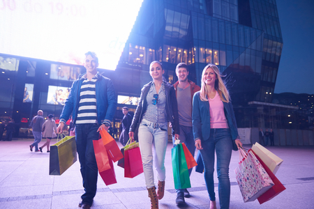Group Of Friends Enjoying Shopping Trip Together group of happy young frineds enjoying shopping night and walking on steet on night in with mall in background