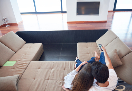 happy families: Relaxed young couple watching tv at home in bright living room