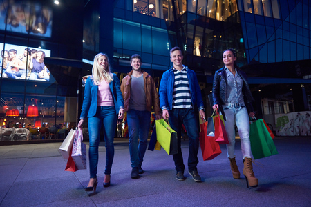 lifestyle shopping: Group Of Friends Enjoying Shopping Trip Together  group of happy young frineds enjoying shopping night and walking on steet on night in with mall in background