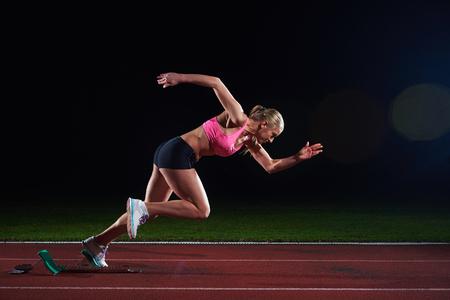 competencia: diseño pixelado de la mujer velocista dejando la salida de la pista de atletismo. Vista lateral. inicio explosión Foto de archivo