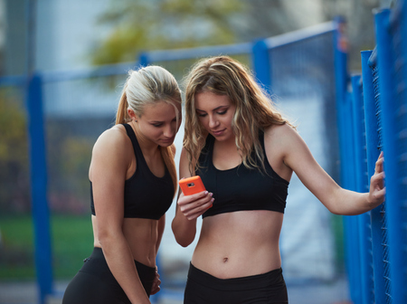 athletics training: teen girls group of friends on athletics training using smart phone Archivio Fotografico