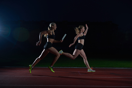 relay baton: woman athletic runners passing baton in relay race