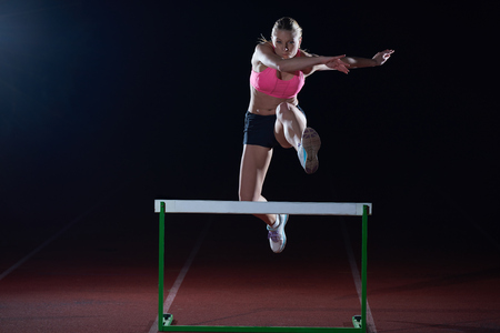 hurdle: Determined young woman athlete jumping over a hurdles