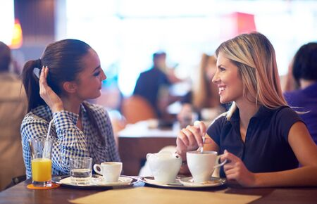 brunette girl: happy girl friends have cup of coffee in modern city restaurant Stock Photo