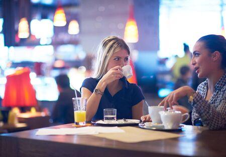 tomando jugo: felices amigas tienen taza de café en el restaurante de la ciudad moderna Foto de archivo