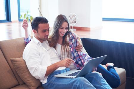 usando computadora: feliz pareja relajada joven que trabaja en la computadora portátil en el interior de una casa moderna Foto de archivo