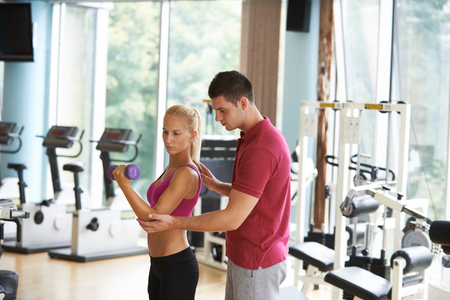 trainer: young sporty woman with trainer exercise weights lifting in fitness gym