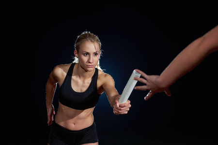 carrera de relevos: woman athletic runners passing baton in relay race