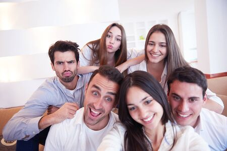 girl home: group of friends taking selfie photo with tablet at modern home indoors Stock Photo