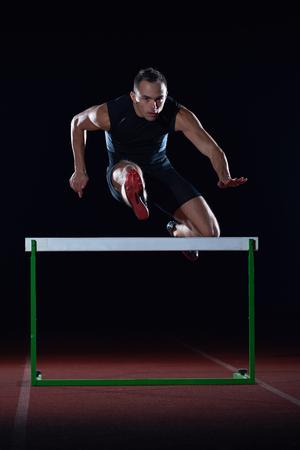 deportista: Hombre atleta saltando sobre unos obstáculos en pista de atletismo carrera Foto de archivo