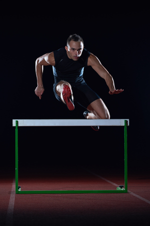 man athlete jumping over a hurdles on athletics race track Stock Photo