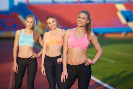 competing: athlete woman group  running on athletics race track on soccer stadium and representing competition and leadership concept in sport