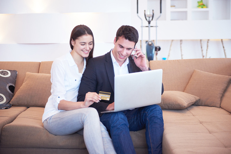 lifestyle shopping: happy young relaxed  couple working on laptop computer at modern home interior