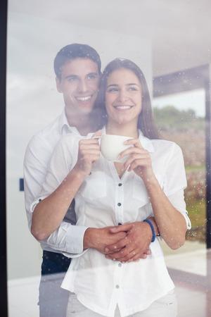 lluvia: relaxet joven pareja beber primer café de la mañana sobre gran ventana brillante en moder interior villa casa