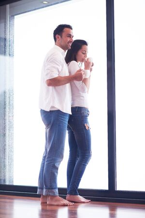 moder: relaxet young couple drink first morning coffee  over big bright window in moder home villa interior
