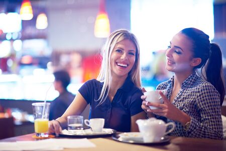 women coffee: happy girl friends have cup of coffee in modern city restaurant Stock Photo