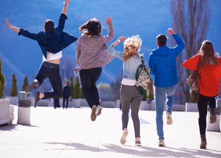 people jumping: grupo de estudiantes felices divertirse al aire libre en el parque del campus universitario Foto de archivo