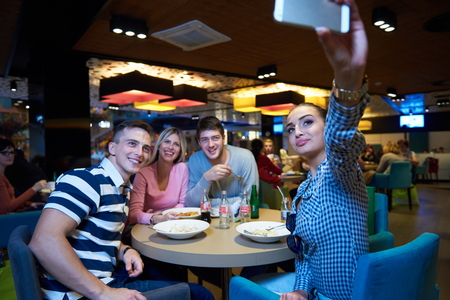 eating fast food: friends have lanch break in shopping mall, eating italian fast food