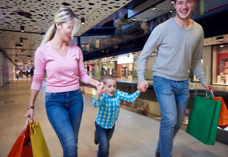 shopping mall: happy  young family with shopping bags in mall
