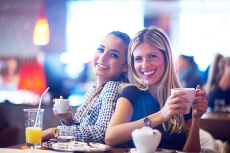happy girl friends have cup of coffee in modern city restaurant Stock Photo