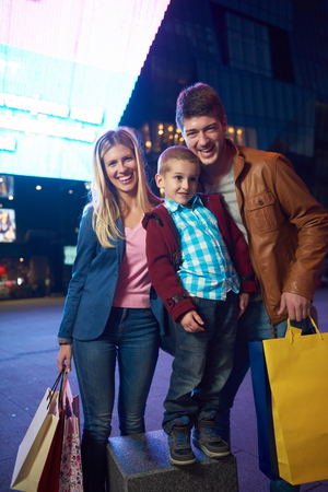 shopping trip: Group Of Friends Enjoying Shopping Trip Together  group of happy young frineds enjoying shopping night and walking on steet on night in with mall in background