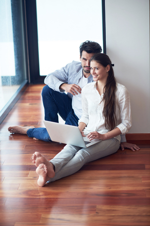 tech support: happy young relaxed  couple working on laptop computer at modern home interior