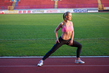 jogging track: young runner sporty woman relaxing and stretching on athletic race track Stock Photo