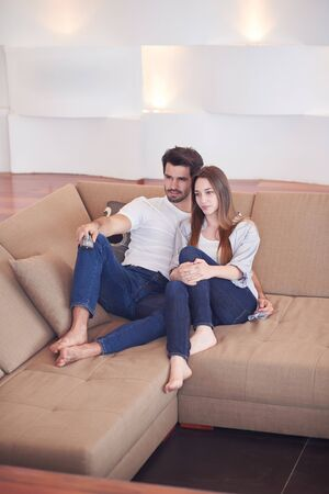 couple relaxing: Relaxed young couple watching tv at home in bright living room