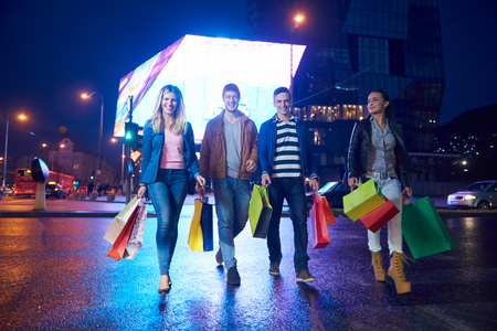 gift bags: Group Of Friends Enjoying Shopping Trip Together  group of happy young frineds enjoying shopping night and walking on steet on night in with mall in background