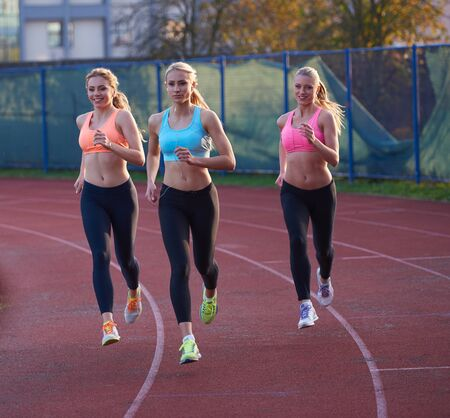 athletics: athlete woman group  running on athletics race track on soccer stadium and representing competition and leadership concept in sport
