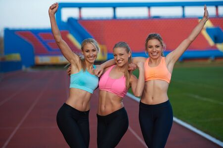 young friends: athlete woman group  running on athletics race track on soccer stadium and representing competition and leadership concept in sport