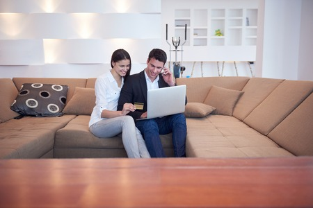 man studying: happy young relaxed  couple working on laptop computer at modern home interior