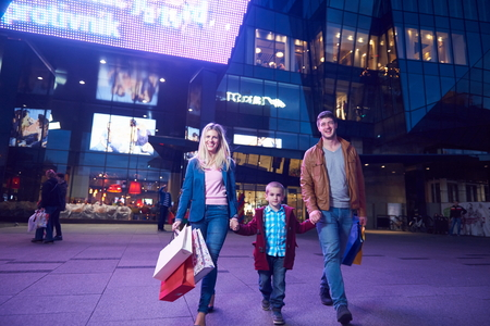 winter fashion: Group Of Friends Enjoying Shopping Trip Together  group of happy young frineds enjoying shopping night and walking on steet on night in with mall in background