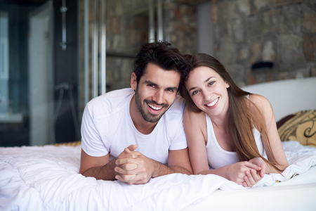 nude in bed: happy young couple relax and have fun in bed