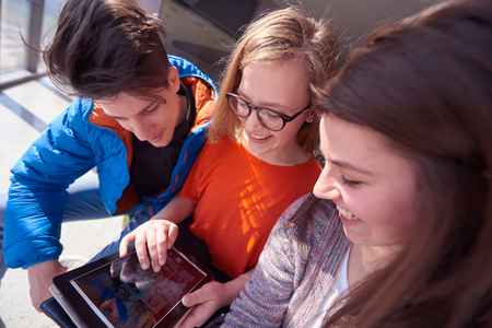 school teens: students group working on school  project  together on tablet computer  at modern university