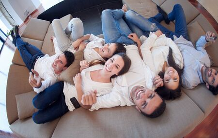family sofa: portrait of happy young group of friends get releax and have fun at modern home interior, top view