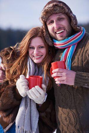 outdoor fireplace: portrait of happy young couple outdoor on winter day drinking warm tea