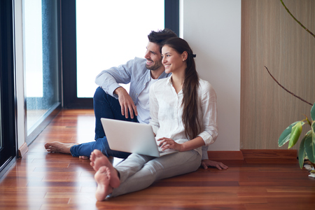 couple relaxing: happy young relaxed  couple working on laptop computer at modern home interior