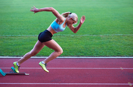 athletics: pixelated design of woman  sprinter leaving starting blocks on the athletic  track. Side view. exploding start Stock Photo