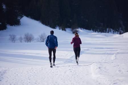jacket: healthy young couple jogging outside on snow in forest. athlete running on  beautiful sunny winter day Foto de archivo