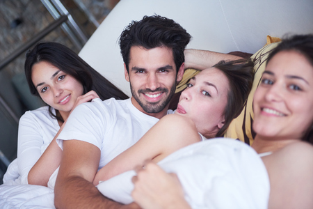 beautiful sex: young macho playboy handsome man in bed with three beautiful sexy woman