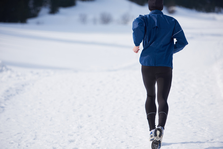 winter park: young  man jogging on snow in forest, bautiful sunny winter day. handsome sporty ahtlete man running