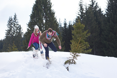 fun day: happy young  couple having fun and walking in snow shoes outdoor in nature at beautiful winter day. Health sport and relaxation Stock Photo