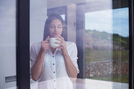 Hermosa mujer joven bebe primer café de la mañana en el interior de la casa moderna con lluvia cae en el vidrio de la puerta de la ventana grande Foto de archivo - 47264553